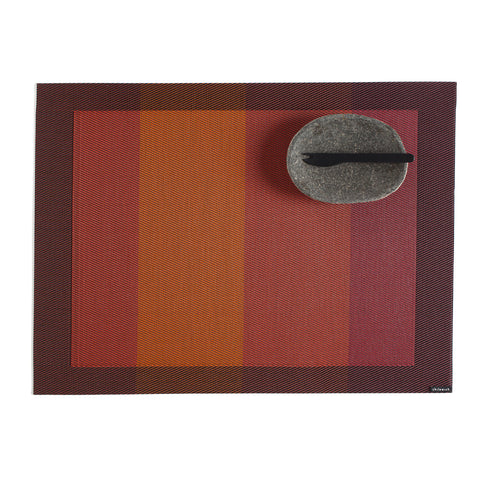 Rectangular woven mat with dark brown border, and inner red and orange blocks of color, alternating light and dark. Small oval granite bowl with black spork shown in upper right corner.