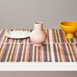 Side view of four basketweave placements with pink, red, yellow, black and white stripes on a clean-edged white table, also showing a white faux marbled dinner plate, pink gourd-shaped ceramic vase and mustard colored ceramic serving bowl with a conical base.