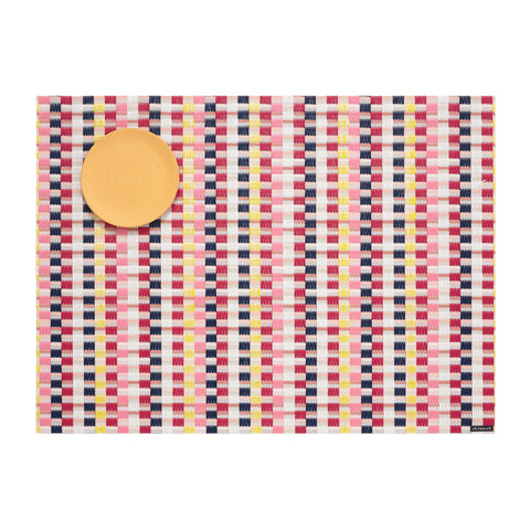Basketweave of pink, red, yellow, black and white vertical stripes on a flat woven field of subtle pink and white stripes, with a round, melon-colored dessert plate in the upper left corner.