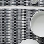 Close up view of one and one-third basketweave placemats with light and dark gray, white and black vertical stripes on a flat woven field of subtle gray and white stripes, with partial views of a white ceramic mug, shallow serving bowl and circular dessert plate.