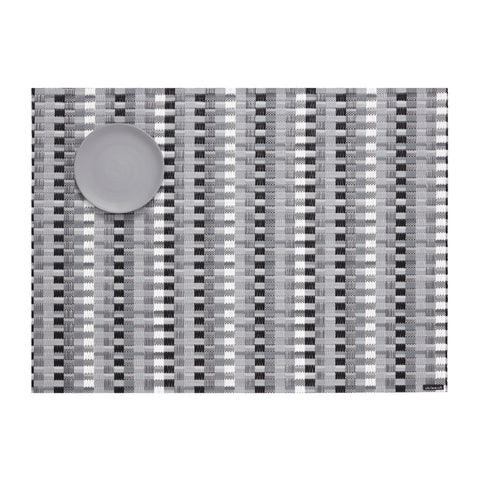 Basketweave of gray, white and black vertical stripes on a flat woven field of subtle gray and white stripes, with a round, medium gray colored dessert plate in the upper left corner.
