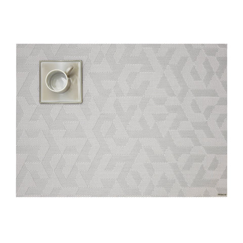 Overhead view of a silver jacquard-woven placemat with a subtle interlocking geometric pattern,  against a white background, with a square shaped ceramic saucer and round mug in taupe, upper left.