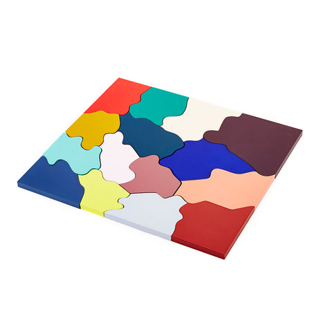 A photograph of an assembled puzzle made up multiple solid colors. Each piece is a unique shape with soft curvy edges that fit together to form a rectangle.