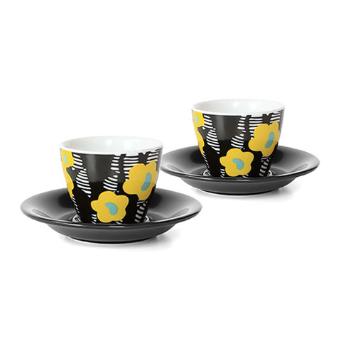 A pair of floral printed espresso cups and saucers. Each cup features a yellow floral print on a black and white background. The saucers are black