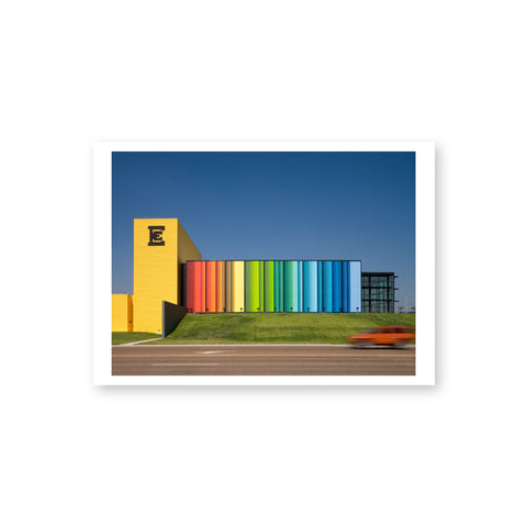 A horizontal postcard with a white border features a daytime exterior view of a contemporary building with a vertical yellow tower, horizontal passageway in rainbow colors red to blue, a square black-framed glass pavilion and a lawn fronted by a street with a moving car.