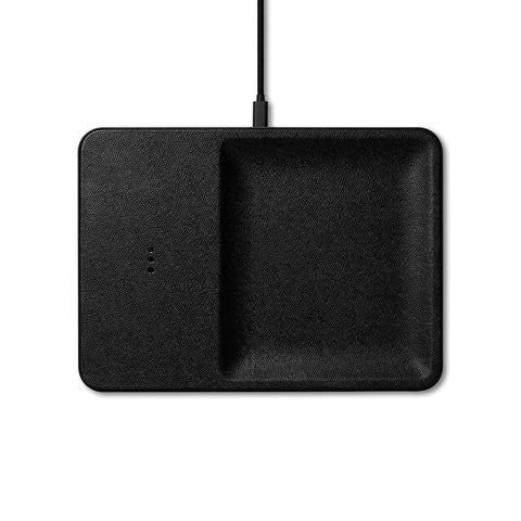 Black, rectangular Catch with rounded corners and a pebbled texture, is 1/3 flat surface, 2/3 concave catch-all. The flat surface has three vertically aligned charging dots in the middle. There is a black charging cable attached to the top edge.