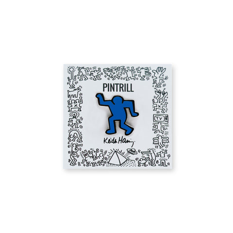 A bright blue Keith Haring character pin at the center of a white square with a border of black and white Haring drawings, the maker's name above, and the artists' signature below in black. The figure dances with arms bent at the elbow, one up, the other down, with one leg bent at the knee.