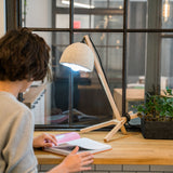 A lifestyle photo of the back of a person seated at a butcher block counter reading an open book by the light of a minimal lamp made from squared lengths of natural wood with a black cord and fibrous lamp shade in a live-work loft environment.