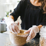 In a Lifestyle photo, a person in a black top in a bright domestic environment wears clear gloves and creates a lamp shade by lining the bowl-shaped mold with seeds.