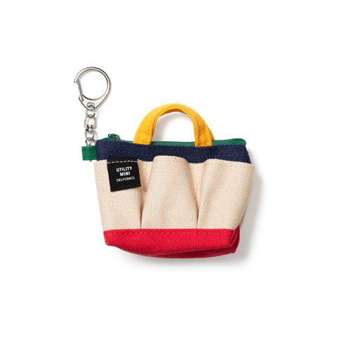 A silver-tone keychain with a small black fabric swatch labelled Utility Mini Delfonics is bold all-caps white print, features a rounded silver keychain clasp connected to 3 interlocking u-shaped links attached to a mini canvas tote featuring a green fabric tab and top-zipper, yellow handles, a dark blue upper band, natural, pleated body and a red, squared bottom.
