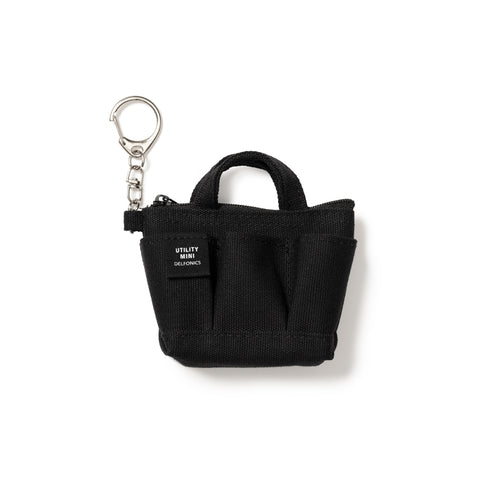 A silver-tone keychain with a small black fabric swatch labelled Utility Mini Delfonics in bold all-caps white print, features a rounded silver keychain clasp connected to 3 interlocking u-shaped links attached to an all-black mini canvas tote featuring a fabric tab and top-zipper, handle, upper band, pleated body and squared bottom.