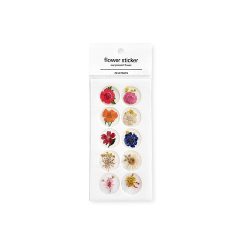 An assortment of 10 round clear stickers with tiny pressed flowers set inside.