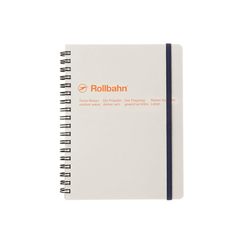 Classic rectangular notebook in gray with a black metal spiral on the left and a black elastic strap on the right. Manufacturers name, logo and 2 lines of neatly spaced text appear 1/3 from the top in orange sans serif letters.