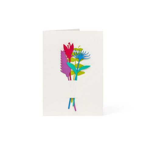 White greeting card with a bunch of five flower and leaf-shaped paper cutouts, in red, purple, blue, teal and chartreuse. Slits in the card hold the cutouts in place.