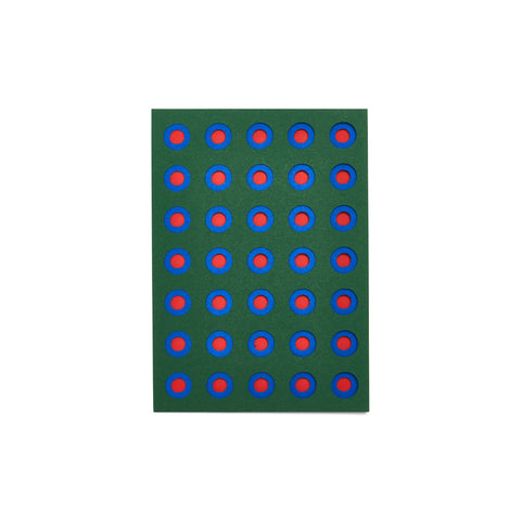 Dark green greeting card with geometric cutouts: rows of concentric circles in blue and red.