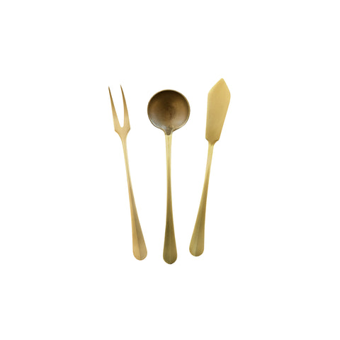 Three brass serving utensils; fork with two tines, shallow spoon, and a small knife.