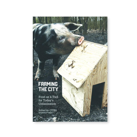 Book cover with photograph of a large black and white spotted big chewing the edge of a small plywood house in a wooded environment. Title in lower left corner in white sans serif font