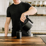 Lifestyle photo of a person pouring water the Clyde Kettle into a cup, in a kitchen with a dark wooden tabletop, white subway tile, and dark wooden shelves.