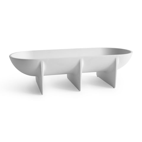 An elongated oval bowl mounted on three planer style legs, finished in matte white.
