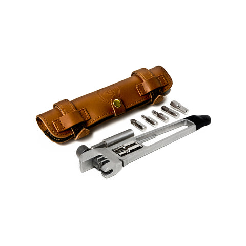 Diagonal arrangement of a brown, oblong leather carrying pouch and compact stainless steel multi-tool set with assorted screw driver heads.