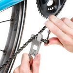 Hands shown holding and using the chain breaker tool on a bicycle chain, with a partial view of the wheel, chain and gears.