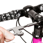 Closeup of a hand using the multi-use tool as a screw driver, positioned parallel to the black handlebars of a partially visible bicycle with a bright pink stem.