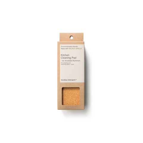 Rectangular, natural cardboard package with gray label for the Kitchen Cleaning Pad Anodized Aluminum, window-cut out reveals yellow, sandy-colored and textured cleaning pad.