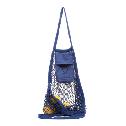 A blue mesh tote is hanging on a hook by one of its handles. The other handle is spread out on the surface below exposing the contents of the bag. Inside the bag, several lemons are visible through the mesh. The Graf Lantz fish logo is visible on an exposed pocket that hangs just below the handle.