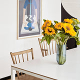 Large blue vase filled with sunflowers, atop a white dining room table and surrounded by maple colored wooden chairs. A framed poster is affixed to the wall.