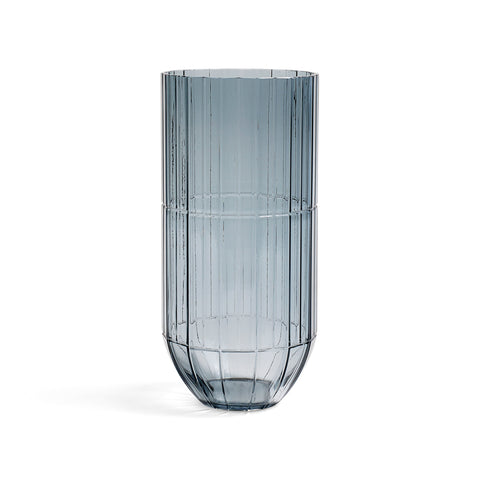 Large transparent vase in a dark blue color. Vase's curved base forms with subtle lines detailing.