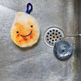 A dirtied white sponge shaped like a water droplet with an embroidered smiley face and a blue loop handle lies at the bottom of a sink, drain to its left.