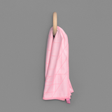 Light pink tea towel with bright pink grid pattern detail. The tea towel is hanging from a wooden hook against a gray backdrop.
