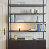 Black Turn On Lamp emits a warm glow on a black bookshelf minimally filled with books and ceramics. .