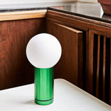 Close-up of the Green Turn On Lamp on a white tabletop with a warm wooden cabinet in the background.