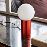 Close-up of the Orange Turn On Lamp on a marble tabletop, its cord extends across the table.
