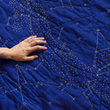 A hand on the left  touches the quilted surface of the Organic Constellation Quilt in Cobalt Blue, which has small round hand-embroidered yellow stars and white lines and circles of embroidery depicting constellations.