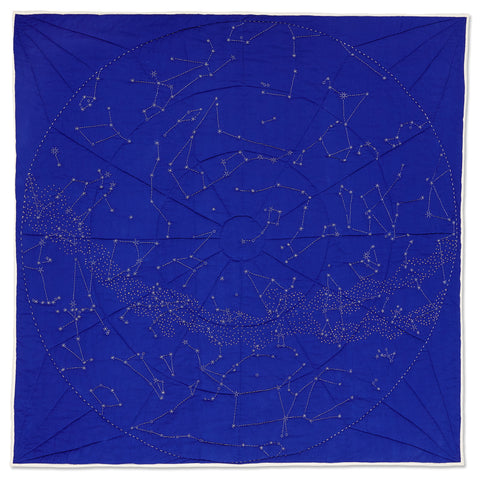 A square, handmade Organic Constellation Quilt in Cobalt Blue with a white, hand-embroidered circular boundary filled with constellations and stars depicting a global view of the night sky of the Northern Hemisphere.