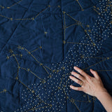 A hand wearing a gold ring, lower right, touches the quilted surface of the Organic Constellation Quilt in Navy, which has small round hand-embroidered white stars and yellow lines and circles of embroidery depicting constellations.