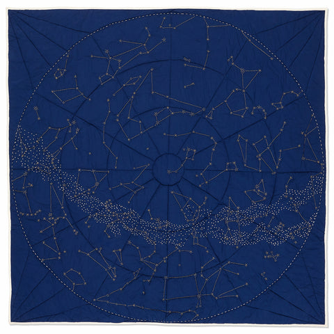 A square, handmade Organic Constellation Quilt in Navy with a white hand-embroidered, circular boundary filled with constellations and stars depicting a global view of the night sky of the Northern Hemisphere.
