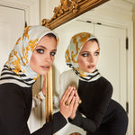 Image of model in black dress wearing scarf on her head and looking into mirror.