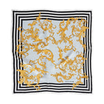 Scarf laid flat, black and white repeating lines as border with pale blue center covered in gold leaf pattern.