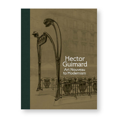 A rectangular book cover, taupe with a full-length strip of dark green, textured binding on the left, and a sepia toned photograph showing the curvy iron art nouveau railings, entranceway and signage for a Paris Metro station against a pale image of a multi-story apartment building in the background. The book's title appears to the left of one of the sign supports in four lines of white text.