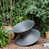 Large matte gray plastic spinning top shaped chair in a verdant patio space