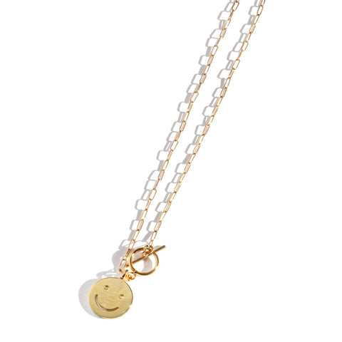 An oversized brass cable link chain necklace with a small flat and round smile pendant and toggle bar clasp.