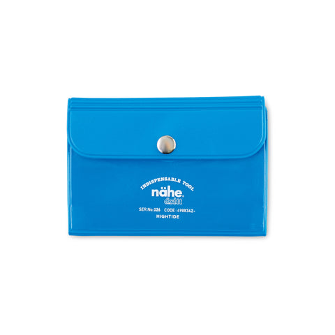"Image of a neon blue card case with a flap closure. Centered on the flap is a single sliver snap. Below the flap imprinted in white is the nahe logo and an arched line of type centered above reading ""INDISPENSABLE TOOL."""