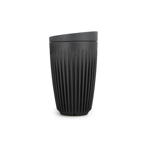A tall, charcoal-colored reusable cup with a flat bottom, tapering shape and overall  pattern of tight vertical ribs, indented towards the base. With a flat, wedge-shaped lid.