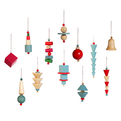 Group of 12 Bauhaus Ornaments, each a different combination of stacked colorful shapes on a string. Colors include red, pale blue, red, magenta, green, and unpainted wood. Shapes include cones, cylinders, spheres, disks, and cubes.