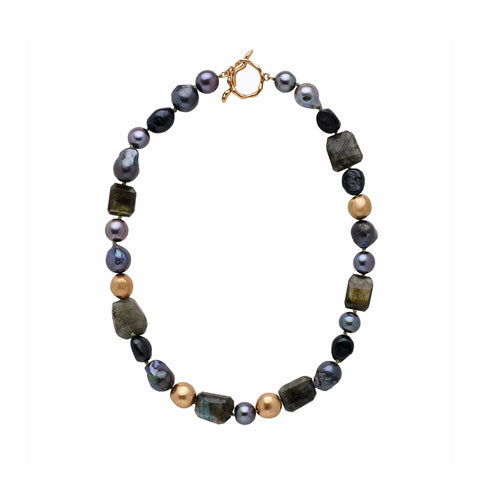 Flat view of the Black Orchid Pearl Necklace. The necklace is chunky and short, with various, irregular black pearls, dark stones, and bronze beads. The closure is a large, bronze, irregular toggle clasp.
