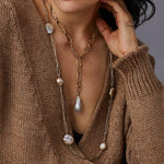 Angle view of a woman wearing the Preza Pearl Necklace, layered with another, shorter necklace. The necklace hangs to just below the deep V of her tan sweater. The image is cropped at her chin.