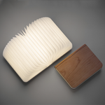 A small book lays flat on an angle with pages open like an accordion, light illuminates from within. Laying next to the open lumio is a closed dark maple Lumio.